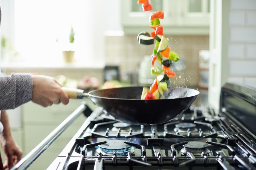 Man tossing fresh vegetables in saucepan