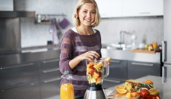 A young woman smiling happily while placing chopped fruit into her blender